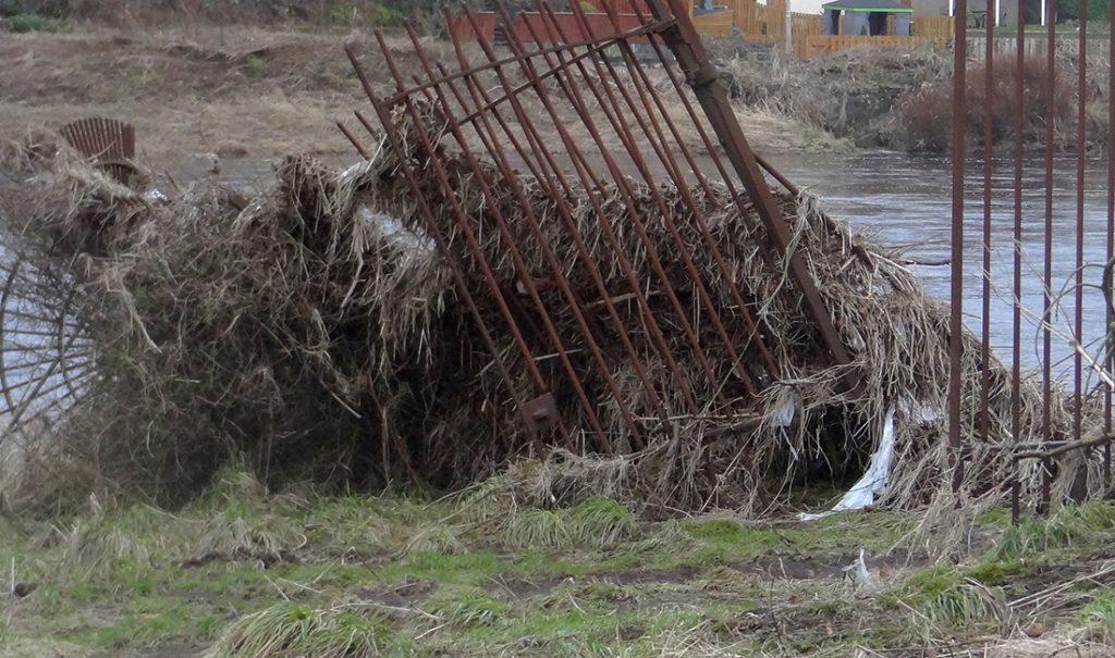 Flood-buckled fence